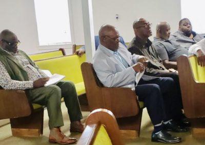 men sitting in pews listening